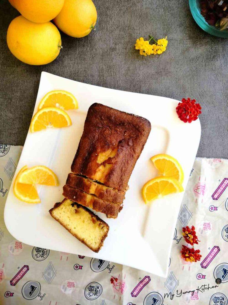 Gâteau à l'orange ultra délicieux servi sur une assiette blanche avec des tranches d'oranges