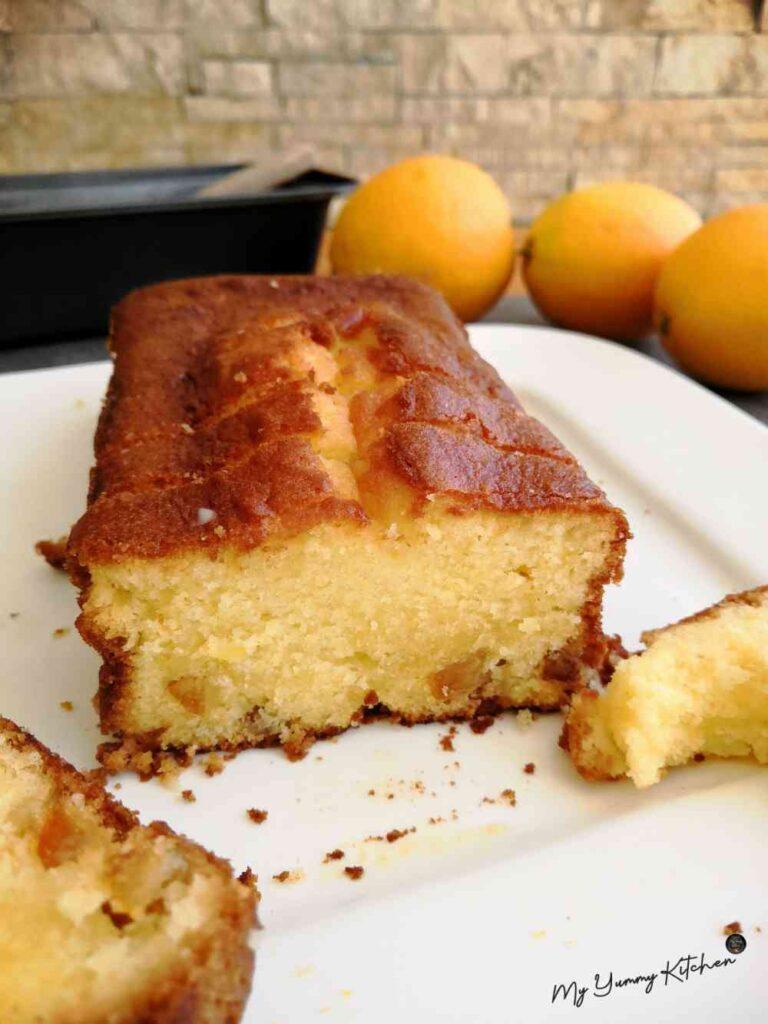 Morceau de cake à l'orange ultra moelleux sur une assiette blanche avec des oranges en décor